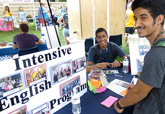student at fair booth table learning about the intensive english program