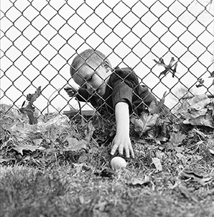 Photo of child in Sunday clothes holding Easter basket, reaching through fence to pick up egg on other side
