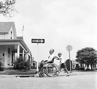 "Photo of young boy pushing man in wheelchair, the opposite direction of a street sign that says ""One Way"""