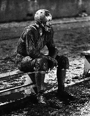 Photo of football player sitting on sidelines covered head to toe in mud