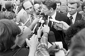Photo of Ronald Reagan surrounded by reporters and microphones