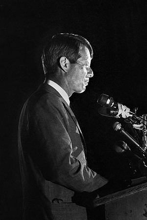 Photo of Robert Kennedy at podium with microphones, speaking