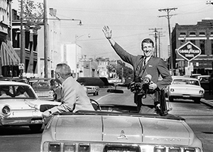 Sonny Brown riding in convertible car, standing and waving while holding a camera in his hand