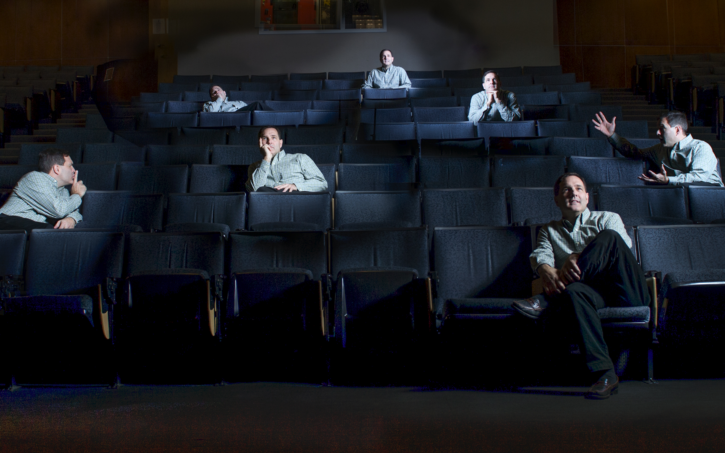Composite picture of man in different poses in theater seats