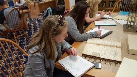Gabby Wilson (front) and Autumn Langen working in the Rice Library Archives on manuscript 19th-century coroners' records for Vanderburgh County.