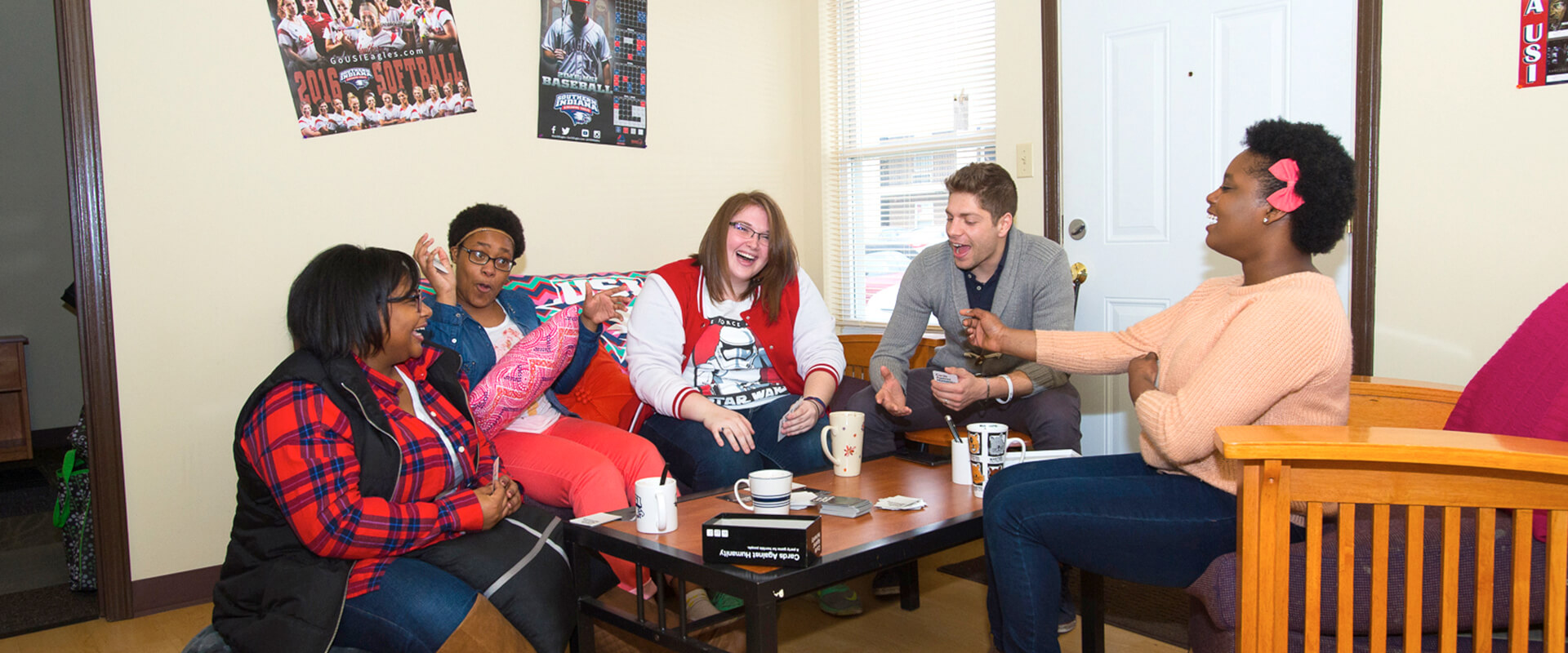group of students playing a game on a coffee table in a campus apartment