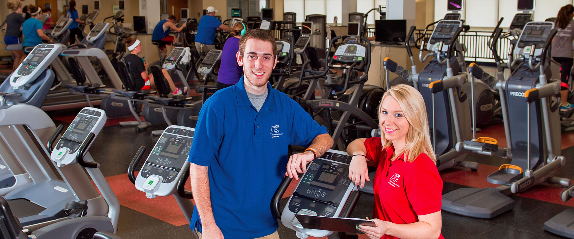 Two trainers standing in fitness center, leaning against treadmill