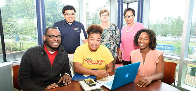 Several students and staff of the multicultural center, posing in front of a laptop