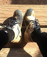 Dirty softball cleats, picture taken from above with sides of shoe visible, so player is sitting down