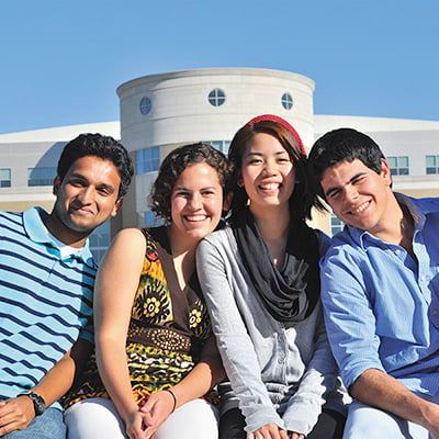 4 international students posing for a photo in front of the library