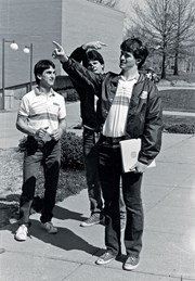 caption contest image of three students standing on USI's campus, two of the students are pointing in opposite directions