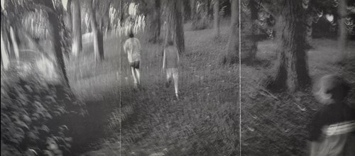black and white photo of two people walking in the woods
