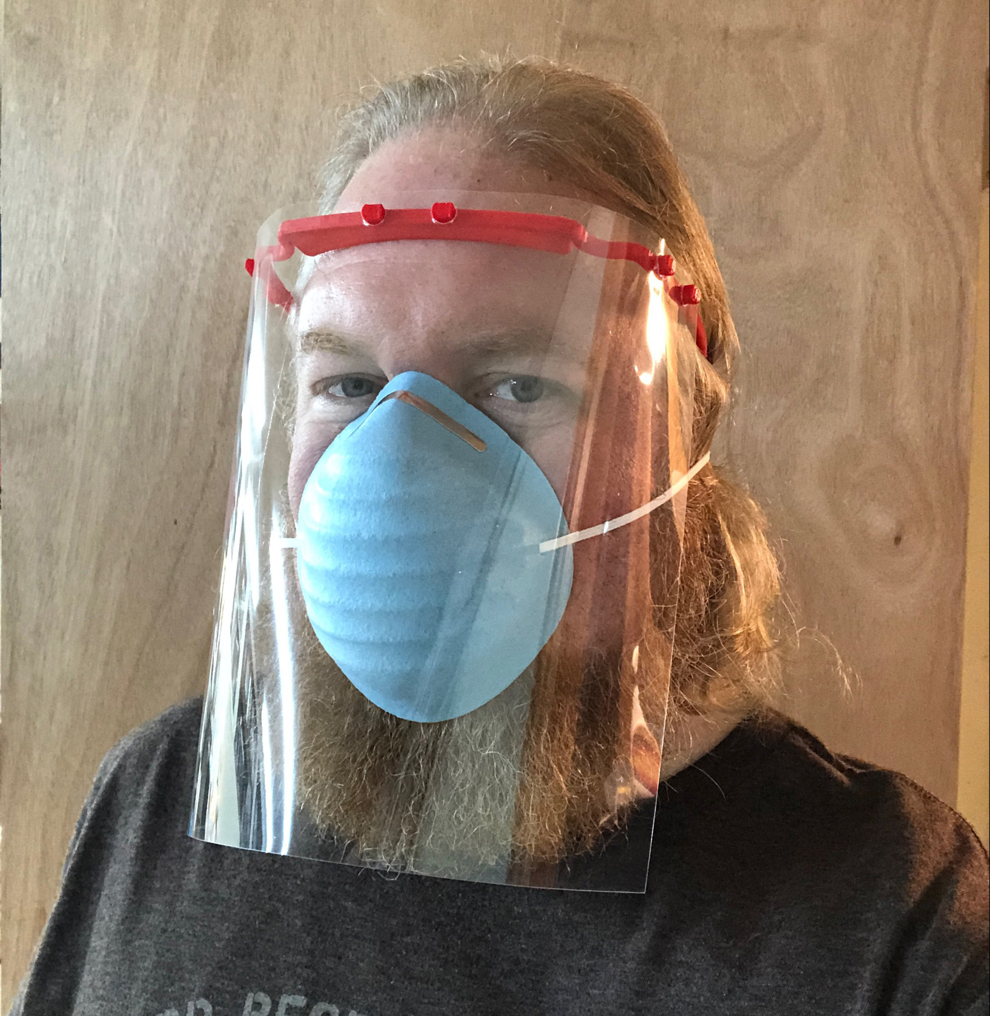 Christopher Norrick wears a 3D printed face shield he created