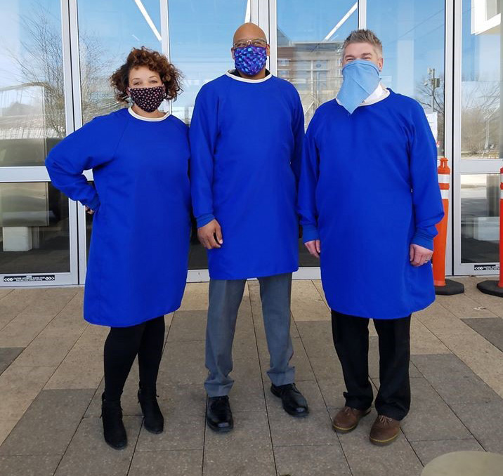 three people stand in blue gowns made by Emily Gartner while wearing face masks