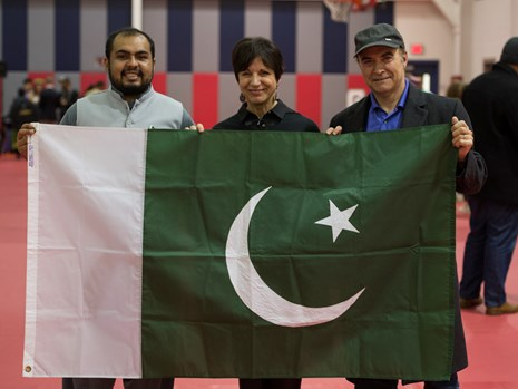 Heidi Gregori-Gahan (center) and her husband Danny (right) hold the flag of Pakistan at a USI event
