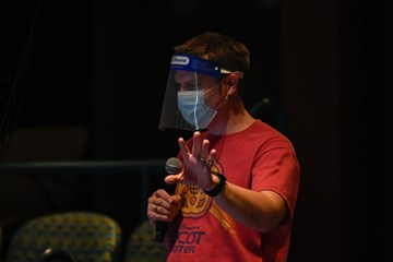 Eric Altheide directs rehearsal of Songs for a New World wearing a mask and face shield