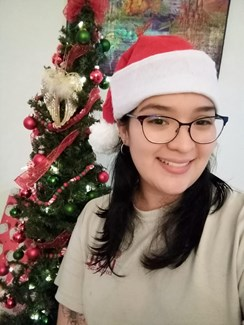Ashley Arauz wearing Santa hat in front of a decorated tree